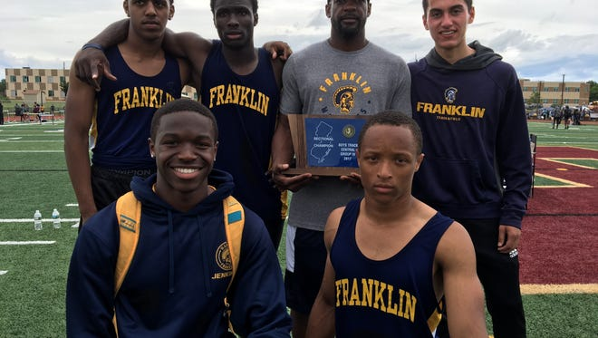 Members of the Franklin High School boys track team pose with the Central Group 4 trophy.