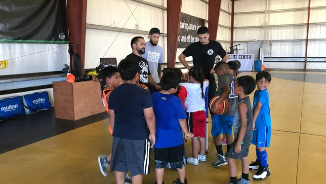 Guam Elite Basketball Academy trainers Dominic Sablan (left), Darren Hechenova (center) and William Stinnett (right) conduct a training session at the Guam Elite Center in Tiyan.  The trio will be a part of the Summer Hoop and Life Skill's Camp.