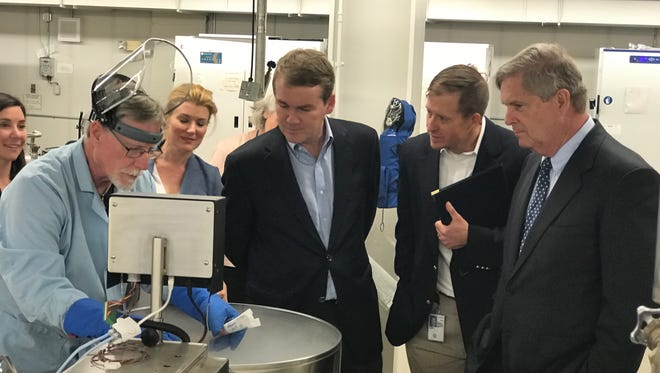 U.S. Sen. Michael Bennet, D-Colorado, center, looks in an extreme cold storage unit while touring the USDA's National Laboratory for Genetic Resources Preservation. Former U.S. Secretary of Agriculture Tom Vilsack, who served under President Barack Obama, far right, also joined the tour.