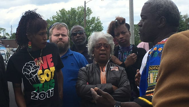 Community activist Andre Lee Ellis addresses community members at the scene of a fatal shooting Sunday at a Citgo station near Hampton and Teutonia Aves. in Milwaukee.