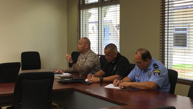 Guam Police Department Chief Joseph I. Cruz, left, speaks to POST Commission chairman Bob Camacho and executive director Dennis Santo Tomas at a meeting about peace officers' physical fitness qualifications test on June 1, 2017.
