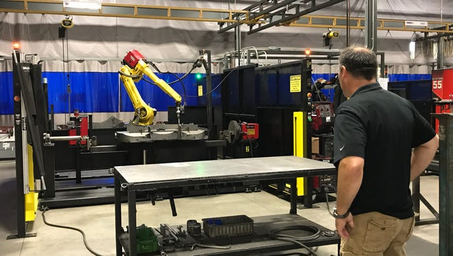 An automation robot is shown during Amerequip's Saturday open house celebrating the completion of an 88,000-square-foot addition to its Kiel facility.