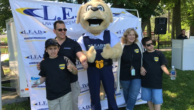 Brothers Dean and Tim Mosca flank Nutley Det. Sgt. Mike Padilla, Leo the Labrador, and Schools Superintendent Julie Glazer on Friday, June 9, 2017, during the Law Enforcement Against Drugs picnic in Yanticaw Park.