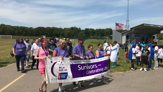 Survivors -- organizers were expecting more than 70 -- carry the banner as the 2017 Wayne-Westland Relay for Life gets underway.