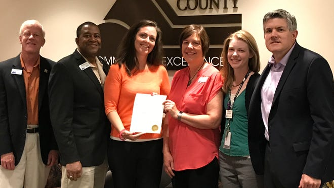 Members of the Larimer County Department of Human Services, center, hold up a proclamation naming June 15, 2017, World Elder Abuse Awareness Day in Larimer County.