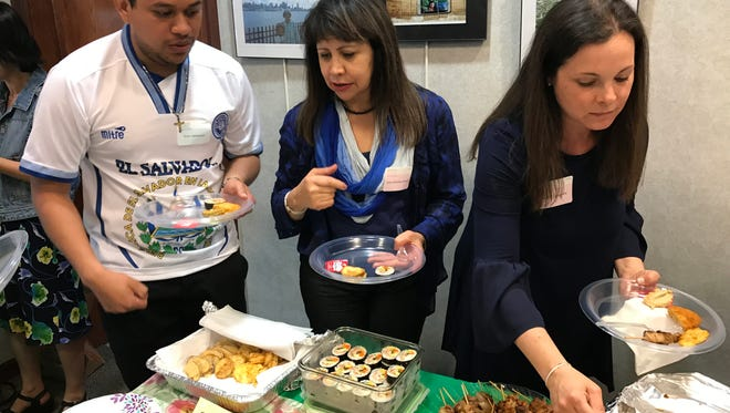 Irvin Velasquez, Julia Morales-Abbud and Janine Lanzisera sample the goodies brought for the 15th annual International Luncheon.
