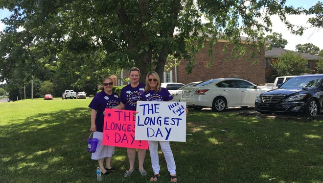Elmcroft of Jackson employees hold signs while fundraising on Old Humboldt Road and Volunteer Boulevard on June 14.