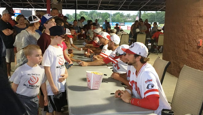 Florence Freedom players sign autographs for kids after their home game on June 18.