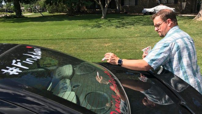 "Chris Paliewicz, the uncle of missing Farmington Hills woman Danielle Stislicki, tags a car window with ""#find dani."""