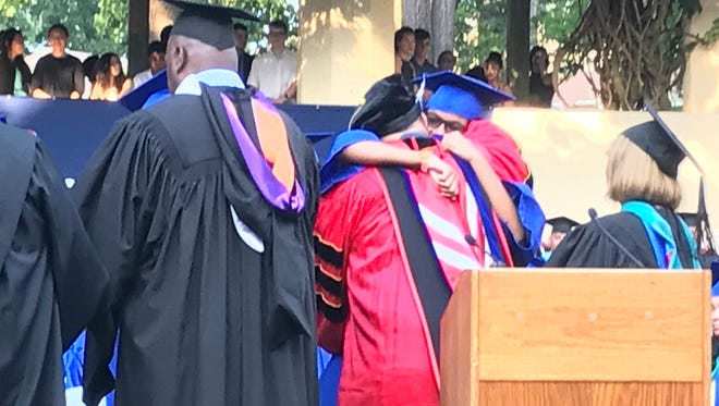 Linez Buxenbaum-Turner receives a hug from father, Montclair BOE member Franklin Turner, after he hands her a diploma at the Montclair High School graduation on June 22.