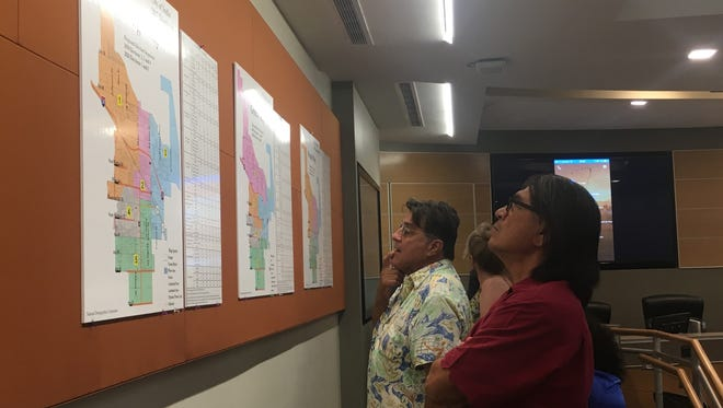 Former City Council member Sam Torres, at right, considers potential district voting maps at the Indio City Council meeting Wednesday, June 21, 2017.