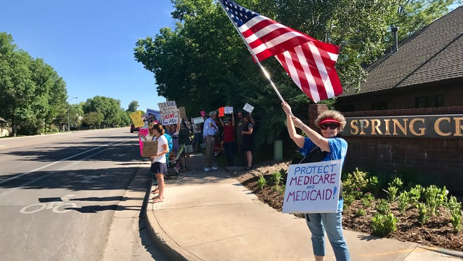 Mary Pridgen, 61, of Fort Collins, waves an American flag Monday while protesting a Republican health care bill in front of U.S. Sen. Cory Gardner's office.