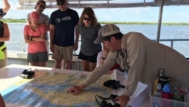"""Adam Wickline (bottom right) shows a group of Wicomico County School District teachers the route they'll take on the Nanticoke River during its """"Summer Institute"""" program on June, 27, 2017."""