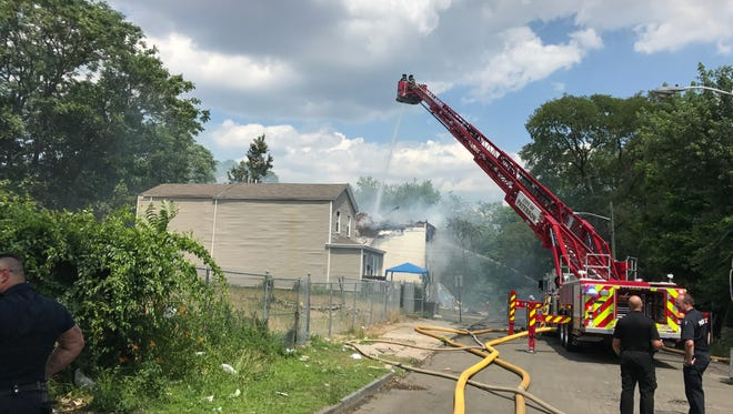 Firefighters pour water onto a house fire on Watson Street on June 30. The building was unoccupied and no injuries were reported.