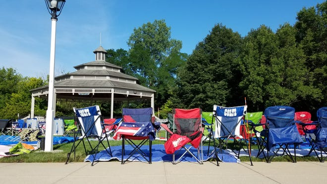 Patriotic and Indianapolis Colts chairs sit on the grass in front of the Carmel Gazebo July 3.