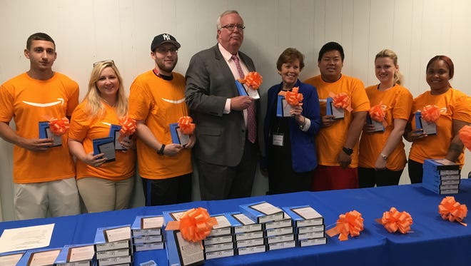 Mayor John McCormac, Woodbridge Public Library Director Monica Eppinger and Amazon representatives show off the Amazon Kindles presented to the library Thursday.