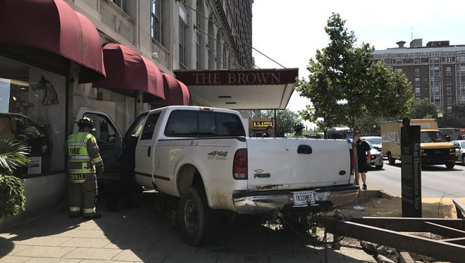 A white truck crashed into the Brown Hotel spilling animal seed all over the road, according to MetroSafe.