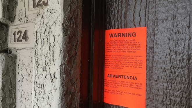An eviction notice hangs on the front door of a Phoenix apartment.