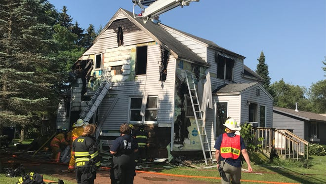 Crews work to extinguish hot spots in the 100 block of Williams St., Schofield, following an early morning fire.
