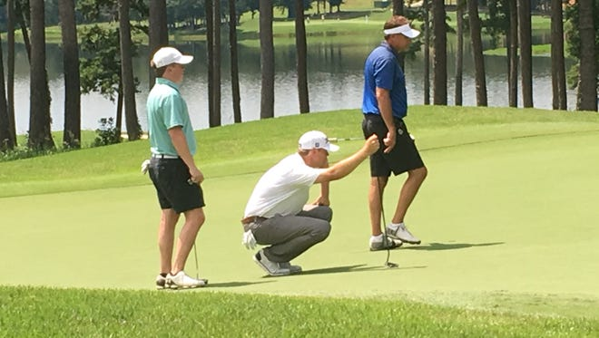 PGA Tour player Patton Kizzire (middle in white shirt and white hat) helping Auburn head football coach Gus Malzahn (right in blue) on No. 9 green at the RTJ Grand National in Opelika during the 2017 Barbasol Championships Pro-Am.