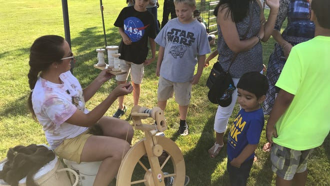 Nicole Blanzy of the Michigan State University Extension-Tollgate Farms works with youngsters to create yarn.