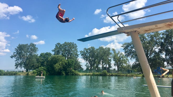On break from his duties as a live lifeguard, Xavier Beach, 17, of Genoa does a flip off the diving board at Genoa Quarry.