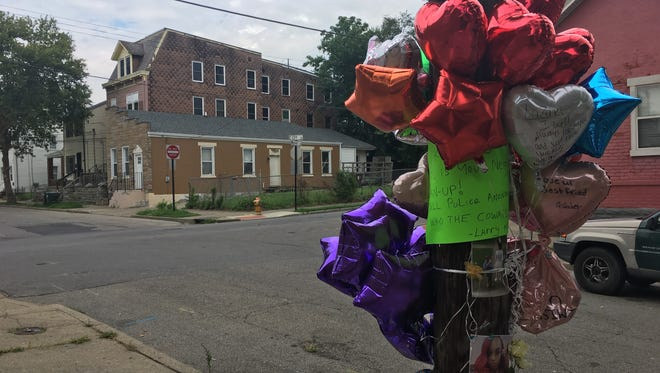 A shrine to Lazuri Collins covers a telephone pole a few feet from where she was shot Saturday morning
