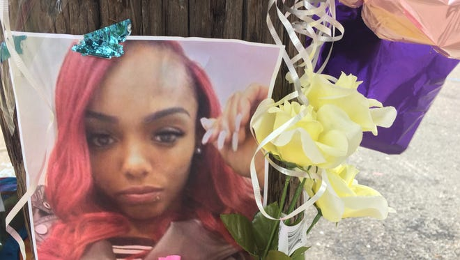 A photo of Lazuri Collins affixed to the telephone poll near where she was shot to death on Saturday