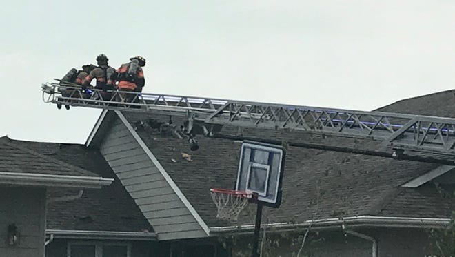 Fire crews break a hole in the roof of a house at 523 N. Solar Drive