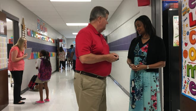 School Board Chairman Bob Alvey speaks with a teacher at Thelma Barker Elementary before classes start Friday.