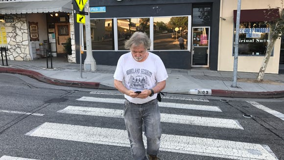 Man crosses the street looking at his cellphone in