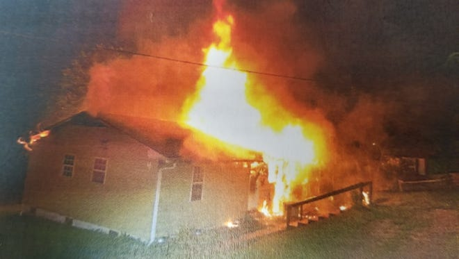 Photo from warrants of the Barnardsville home on Rocky Lane on fire Thursday night. The home housed three people who are have been charged with accessory after the fact of first degree murder.