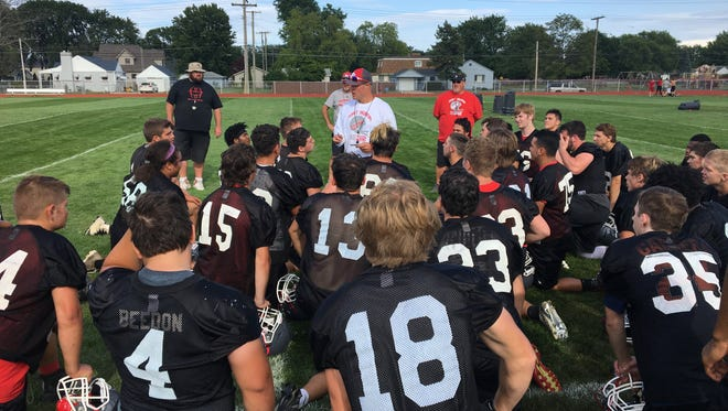 Port Huron High School football coach Ryan Mullins talks to his player at the end of practice Monday at Port Huron High School.