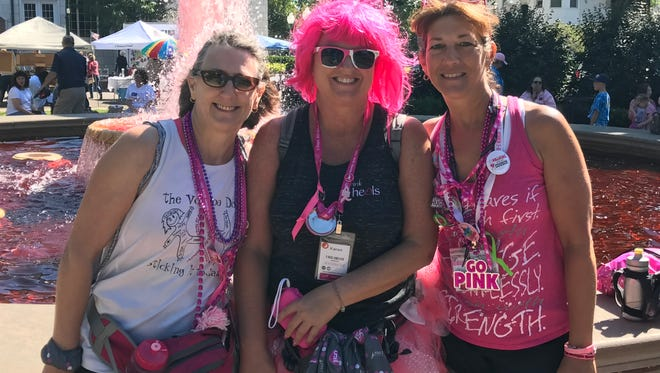 Walkers Ellen Banta (from left), Karen Rush and Denise Mintz take a break at the fountain in Kellogg Park during last weekend's Michigan 3-Day.
