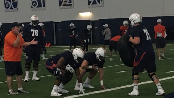 Auburn offensive line coach Herb Hand directing practice instructions to Darius James (78) as Prince Tega Wanagho (76) watches.