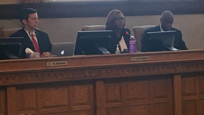 City Council Members P.G. Sittenfeld, left, and Charlie Winburn, right, listen to Yvette Simpson talk about her opposition to the zoning changes for the $550 million expansion of Cincinnati Children's Hospital Medical Center into the Avondale neighborhood.