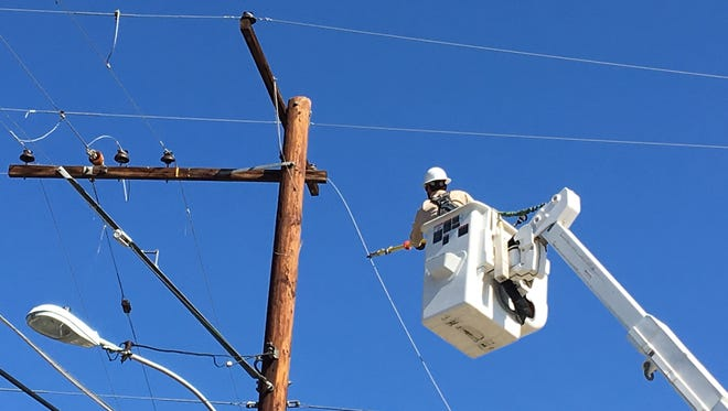 A worker fixes power lines in Southern California. Desert Sun file photo.