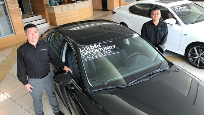 Phil Leddy, left, and John Kim next to a Lexus at the showroom in Tamuning. Lexus owners can help the American Red Cross by taking a test drive throughout August.