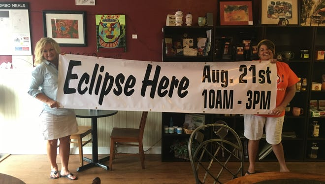 Nyra Syers and Josie Watson stand with the Union County Chamber of Commerce Eclipse Party sign.