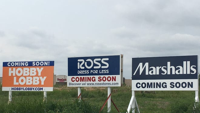 """""""Coming Soon"""" signs line the street on the outskirts of the Lake Lorraine mixed-use development southeast of 26th Street and Marion Road."""