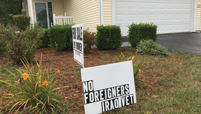 "James Prater of Mason moved his signs apart and reworded one slightly after state officials said he was violating anti-discrimination laws with his ""No foreigners"" sign."