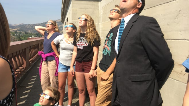Governor Steve Bullock watches the solar eclipse with his family and others from the dome of the state capitol building on Monday.