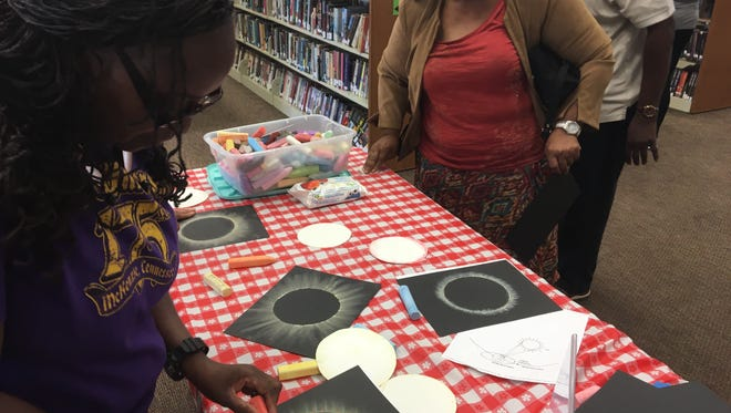 Jackson-Madison County Library visitors draw their own solar eclipse Monday before the library's viewing party.