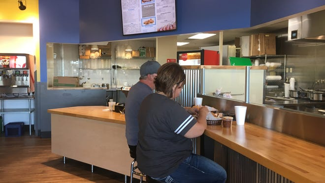 Lisa Lenling of Sioux Falls eats Tuesday at Cluckin' Good Chicken & BBQ on East 10th Street.
