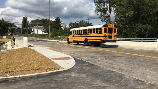 A Mansfield City Schools bus drives across the newly opened Bowman Street bridge Thursday, Aug. 24, 2017. The roadway reopened Thursday after it was closed nearly five months to allow for a bridge replacement.
