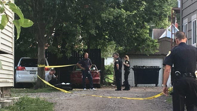 Police investigate the backyard and driveway of 1439 Henderson Avenue. A person was set on fire near the home and later died, according to police.