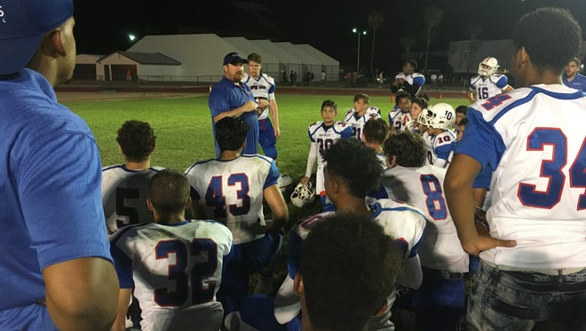 First-year coach Seth Millican talks with Moon Valley players after the team's 41-0 win over Thunderbird in the season opener on Friday, Aug. 25, 2017.
