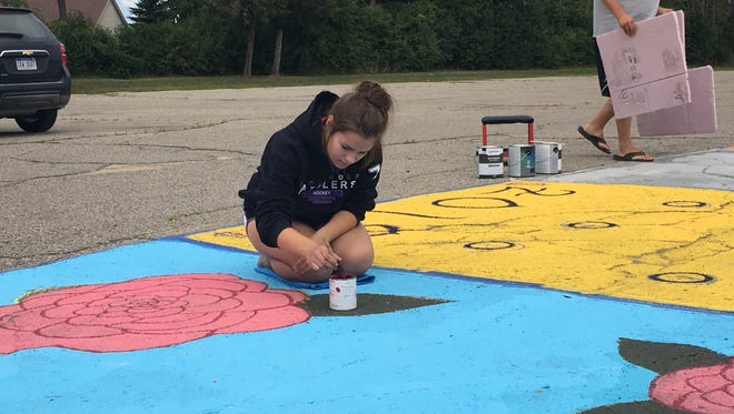 Madilyn Morris, 17, finishes up flowers on her parking spot. This is the first time Yale High School has allowed students to personalize parking spaces.