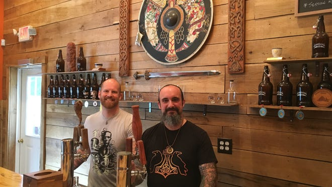 The Brimming Horn Meadery owners J.R. Walker, left, and Jon Talkington behind the bar. The two built the inside of their mead hall by hand.