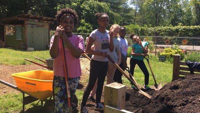 Kids works in a garden as part of FEAST programming.